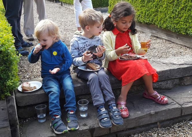 Mmm cake, three younger garden visitors enjoy chocolate cake after an afternoon of garden exploration