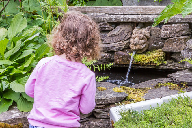 A little girl watching the water feature at Duncan Street garden